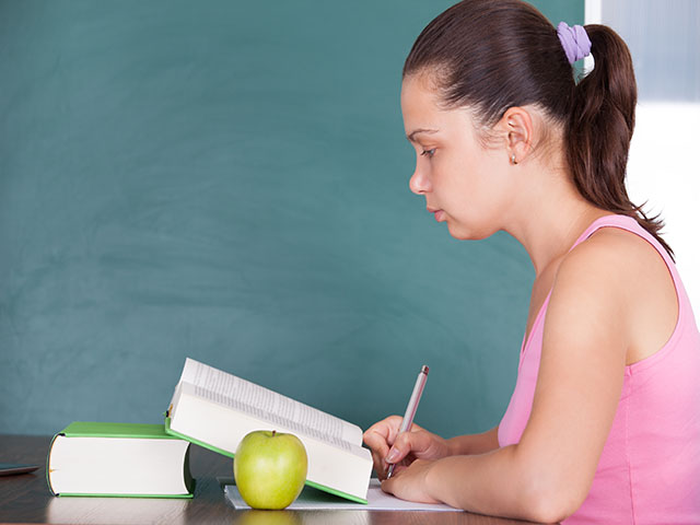 Portrait of young female student writing on paper beside green apple